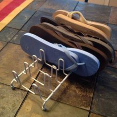 This idea has been all over Pinterest, but I wasn't able to find the original source. Would love to know who it is! Use a plate rack to organize your flip-flops.