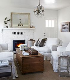 White Living Room White Living Room A Pottery Barn sofa and custom chairs flank a pine trunk in this living room. The homeowner shot the feather photo that hangs on one wall, as well as the skull image that adorns a pillow from Archival Decor. Living Room Decor Cozy, Living Room White, White Rooms, Living Room Furniture, Cozy Room, Apartment Furniture, Living Room Designs, Living Spaces, Small Living