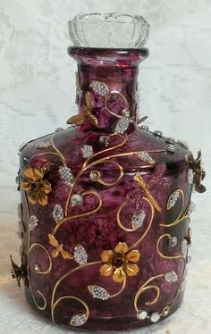 Artfully Musing. This particular bottle is colored with Alcohol Ink.  The gold stems and leaves are metallic stickers.  The leaves are filled with microbeads and rhinestones were added to the round areas.  The final touches are the brass dragonflies, bees and flowers.   The stopper is a crystal drawer pull.