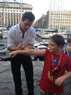 Omg how cute is henry signing that little boys arm