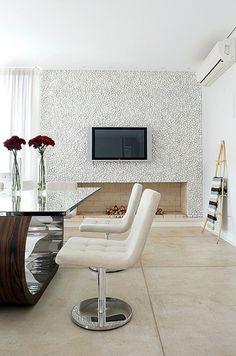 Na reforma da casa no Jardim Marajoara, em São Paulo, projetada por Lica Cukier, o piso é de cimento queimado e as paredes, brancas. Para valorizar a área da lareira, foram usados apenas seixos da mesma cor