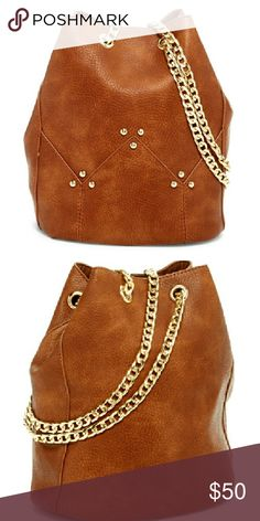 """NWT Brown Bucket Cross-Body by Pink Haley NWT, this beautiful bucket-style cross body bag is a lovely caramel brown color. This trendy bag features gold-tone chain straps. Dual adjustable chain shoulder straps, in a drawstring closure style. Approximately 9.75"""" H x 6.75"""" W x 6.5"""" D, 12"""" handle drop and 12""""-25"""" strap drop. Faux leather exterior, fabric interior. Pink Haley Bags Crossbody Bags"""