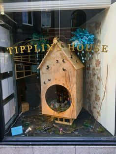 Imbibing Birdhouse - Spring Window Giant birdhouse home to a whimsical nest of orange flavoured whisky, glasses, a perfume bottle, shiny beads and silver cutlery- a boozy magpie's dream. Also features bottle birds foraging and perching among the moss, mushrooms and branches. Paper clouds rain down spring showers as butterflies gather.