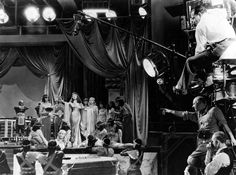 Cecil B. DeMille points the way to his Cleopatra, Claudette Colbert. Directly below the director is cinematographer Victor Milner