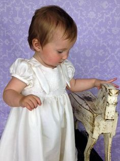 Rose by Okika, features embroidered lace on the bodice and flat bows on the shoulders.  Perfect for the baby that is now toddling.