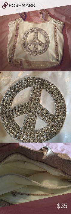 Peace sign purse White faux leather purse with silver peAce sign with glitter and silver gems. Has light brown trim. Super spacious inside with phone pocket and inside zipper as well as a zippered middle section (for iPad or computer depending on size) . Also has a zipper top to close whole inside.its in absolutely perfect condition. Bags Shoulder Bags