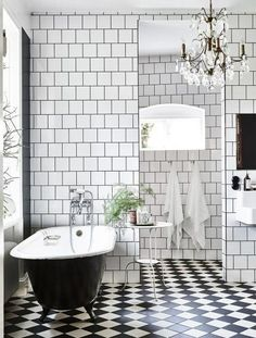 Luxe bathroom with checkered tile, freestanding tub, and chandelier