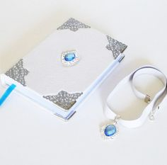 White-off #leather #journal with #blue #pendant and necklace set of two for women and girls. Wonderful handmade art journal, with silver ornaments and light blue glass cristal pearl pendant in front Diary Notebook, Notebook Ideas, Pendant Set, Pearl Pendant, Leather Necklace, Leather Jewelry, Creative Notebooks, Leather Photo Albums, Leather Diary