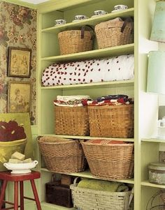 I love everything about this shelf in the laundry room. I LOVE the cheerful light celery color. I love the baskets and the few little accents of red.