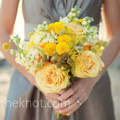 The bridesmaids carried a mix of – yup -- yellow blooms, incuding cabbage roses, mums, billy balls, and ranunculus. The bride carried similar flowers in white.