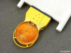 Gelbe Blinkleuchte mit orangefarbenem Reflektor auf grauem Asphalt liegend an einer Baustelle in Münster im Münsterland