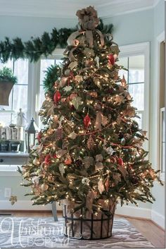 Christmas Tree with bottom wrapped in burlap inside wrought iron basket & decorated  with Red & White Ornaments & burlap bows & red bead garland