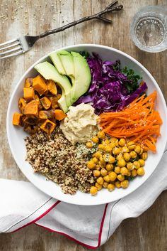 Roasted chickpeas, roasted sweet potatoes, rainbow quinoa, purple cabbage, carrots, hemp seeds, hummus, and avocado.