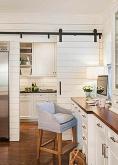 LOVE this Beachy-Inspired Kitchen: with tons of white, sliding beadboard barn doors, light blue hues & wooden countertops.