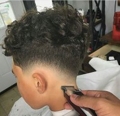 Messy Curls On Top With Low Fade This is another cute hairstyle for black boys. The look is just amazing and features loose curls on the top combined with low fade. Overall, it's a nice haircut to have for both formal and casual routines. Boys Curly Haircuts Kids, Mixed Boys Haircuts, Little Black Boy Haircuts, Black Boy Hairstyles, Boys Fade Haircut, Kids Hairstyles Boys, Toddler Haircuts, Baby Boy Haircuts, Boys With Curly Hair