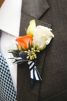Orange and white rose boutonniere with black and white striped ribbon and sea holly on a charcoal gray groom's suit with a patterned tie for a seaside wedding via Beautiful Blooms.