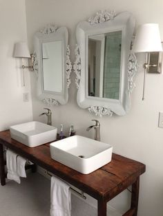 White bathroom with vessel sinks and wood table as vanity  Like the table vanity: