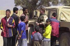 Coalition soldier talks with Iraqi civilians