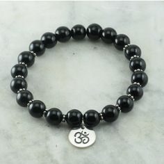 The Perception Chakra Bracelet is made from 21 black onyx mala beads. Sterling silver flowers are added for color. It is completed with a sterling silver OM charm. This Yoga Bracelet is best for: Improving Vitality, Stamina, 1st, 3rd, and 6th chakras #blackonyx #yogabracelet #chakrabracelet #vitatlity