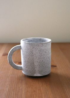 This is a tall handmade ceramic mug made of speckled stoneware clay. It is shown here in a matte white glaze. Smooth to the touch, this is