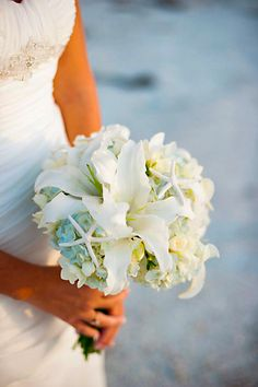 Take a look at the best beach wedding flowers in the photos below and get ideas for your wedding! Chic starfish accent a bouquet of hydrangeas and lilies. Beach wedding bouquet Image source Wedding Ideas: How to Plan a Rustic… Continue Reading → Lilly Bouquet Wedding, Beach Wedding Boutonniere, Beach Wedding Bouquets, Beach Wedding Reception, Beach Wedding Decorations, Bride Bouquets, Bridesmaid Bouquet, Cascading Bouquets, Wedding Ideas