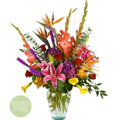 grand display brimming with tropical flowers and Gladiolus in a tall and airy design in a recycled glass ming glass vase