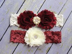 Wedding Garter Set This beautiful bridal garter set features ivory and burgundy rosettes with crystal embellishments. The lace is in the colors ivory