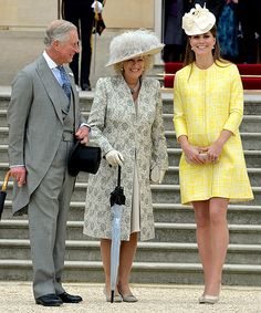 Kate Middleton shows off her baby bump in a yellow coat dress as she mingles with Prince Charles, Prince of Wales, and Camilla, Duchess of Cornwall, at the Queen's annual Garden Party on the grounds of Buckingham Palace on May 22, 2013.