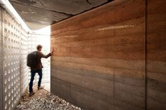 A rammed earth wall in different soil types gives the project a layered…