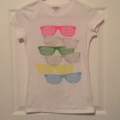 Exodus X tee. Exodus is X tee shirt size medium. White with neon colored sunglasses and silver sparkle funky glasses. Used but no rips and no stains. Exousia X Tops Tees - Short Sleeve