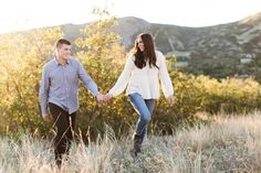 An outdoor airy couple lifestyle session at the capitol of Utah and a beautiful field ~ Utah - Engagement - Candids - Vest - Dress - Candids - Love - Bride and Groom - Posing - Trees - Green - Golden Hour - Film - Capitol - Smiles - Cuddles - Brown Hair - Field - Blue Shirt - White Shirt - Blue Jeans - Clean - Airy - Walking - Holding Hands