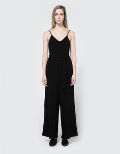 Simple jumpsuit from Farrow in Black. Thin straps. Gentle V-neckline. On-seam side pockets. Wide straight leg. Detachable tie belt.     • Jersey  • 96% polyester, 4% spandex  • Hand wash cold, dry flat