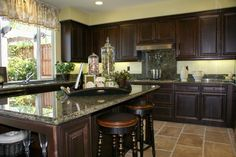 Dark wooden cabinets and gray/black toned countertops, middle island