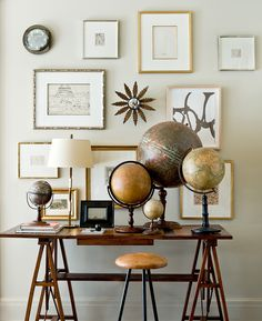 Suzanne Kasler uses collections to create impact, like this collection of antique globes which pairs beautifully with warm wooden furniture pieces and a gallery wall of art with gilded frames | From Suzannes new book, Timeless Style