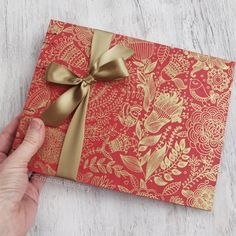 A stylish Indian themed floral pattern in gold printed on a scarlet red handmade lokta paper. Finished with a gold satin bow. Size:MEDIUM (outer dimensions) * Pages measure x - book in Indian Theme, Gold Print, Party Guests, Wedding Veils, Lace Flowers, Handmade Wedding, Wedding Guest Book, Hand Stitching, Photo Booth
