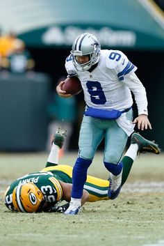 Dallas Cowboys vs. Green Bay Packers - Quarterback Tony Romo #9 of the Dallas Cowboys carries the football against Nick Perry #53 of the Green Bay Packers during the 2015 NFC Divisional Playoff game at Lambeau Field on January 11, 2015 in Green Bay, Wisconsin. (Photo by Joe Robbins/Getty Images)