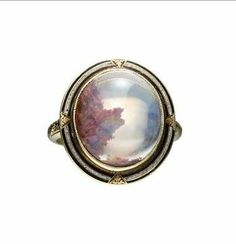 A victorian ring, features a cabochon-cut opal set in an engraved 14k gold ring with black and white enamel detailing. The amazing part, though, is that opal — the stone has inclusions that look like reddish-brown moss