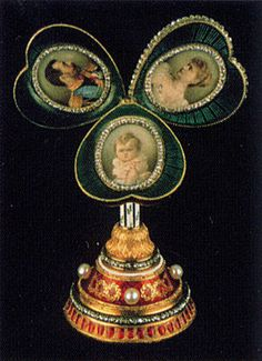 An gem-set enameled gold heart-shaped frame, the strawberry red enamel heart set with the date 1897 in rose-cut diamonds upon a hexagonal tapering shaft painted with spiraling green enamel foliage against an opaque white enamel ground. When the shaft is depressed, the heart opens into a three-leaf clover. Each leaf is enameled green over a guilloche sunburst pattern and contains a diamond-set oval framing miniatures of Tsar Nicholas II, Tsarina Alexandra Feodorovna and their infant daughter