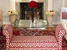 A traditional bench is covered in a geometric red pattern, while a glass and chrome coffee table adds a contemporary touch to the living room