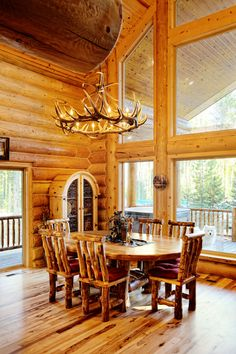 Dining room of a log home with elevated ceiling and floor-to-ceiling windows