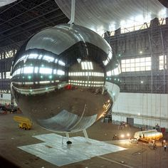 The PAGEOS (PAssive Geodetic Earth Orbiting Satellite) during a test inflation in a blimp hangar at Weeksville, NC, USA, 5 August 1965. The satellite was a 30,5 m (100')-diameter inflatable sphere made of 0.5-mil thick aluminized polyethylene...