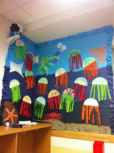 Jellyfish made from strips of colored crepe paper for a summer theme in the classroom.