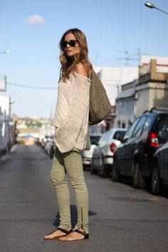 It all comes together in such an integrated manner on this 'street style' outfit:light loose perforated sweater in ivory color + military green zippered cargo skinnies + black leather flat thong sandals with buckle strap + olive green embossed leather tassel hobo bag + black 'wayfarer' sunnies.A comfy and relaxed yet stylish casual look with a flirty touch.