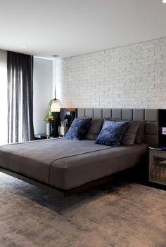 No quarto do casal, como a moradora é cadeirante, a cama fica suspensa para que a cadeira de rodas se encaixe. A parede foi revestida com tijolos brancos.