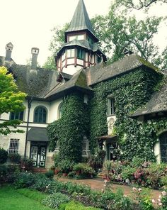 English Tudor house, with ivy up walls and around windows, lovely gardens, tall tower with pointed arch roof. Nice!