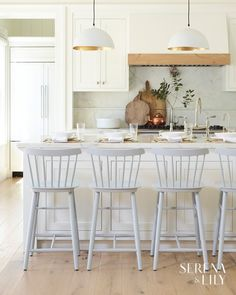 We love this modern, white kitchen with sleek light pendants and classic Windsor counter stools.
