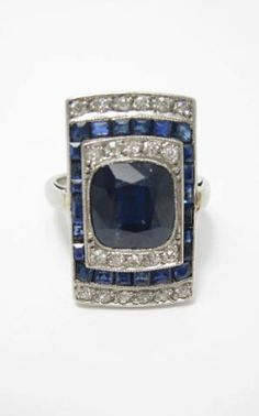 An Art Deco sapphire and diamond plaque ring, French.  The shaped rectangular plaque set centrally with a cushion-cut sapphire bordered by a row of old round brilliant-cut diamonds, all surrounded by a frame of calibré-cut sapphires, with a further row of old round brilliant-cut diamonds to each end, between plain shoulders to a plain hoop