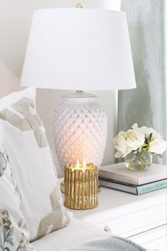 Need some bedroom decor inspo for your elegant home? Check out this simple nightstand setup. Start by stacking some hardcover books and on top of them adding a small vase with white flowers. Next to that, style a gold Thompson Ferrier Sagano candle that's bound to standout against the white furnishings. Finally, add some height to the decor with a tall white lamp and light your candle to fill the room with aromatherapy. pc: @tuftandtrim #ThompsonFerrier