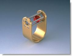 Abrasha2.jpg (487×377).....An 18K gold ring uses five stainless steel pins to enclose a ruby ball.