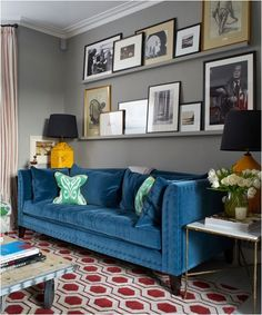 Blue velvet sofa and wall shelves painted the wall color. Cozy.